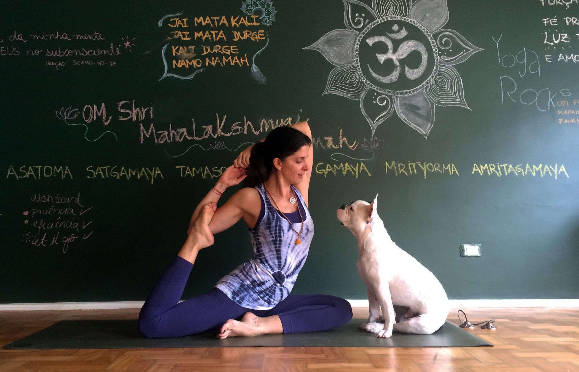 Carla e seu cão Budha na sala de Yoga de porta amarela.